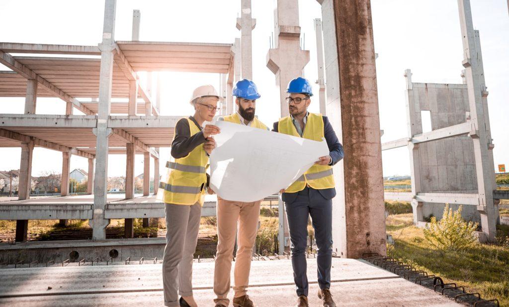 Cette image montre trois personnes dont une femme et deux hommes sur un chantier de construction avec à la main un grand plan. On sent qu'ils discutent sur un sujet concernant le plan qu'ils ont en main.