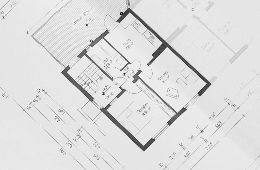 Image montrant un plan de RDC côté avec une chambre, un salon, une cuisine, une salle de bain, une cage d'escalier et une terrasse.