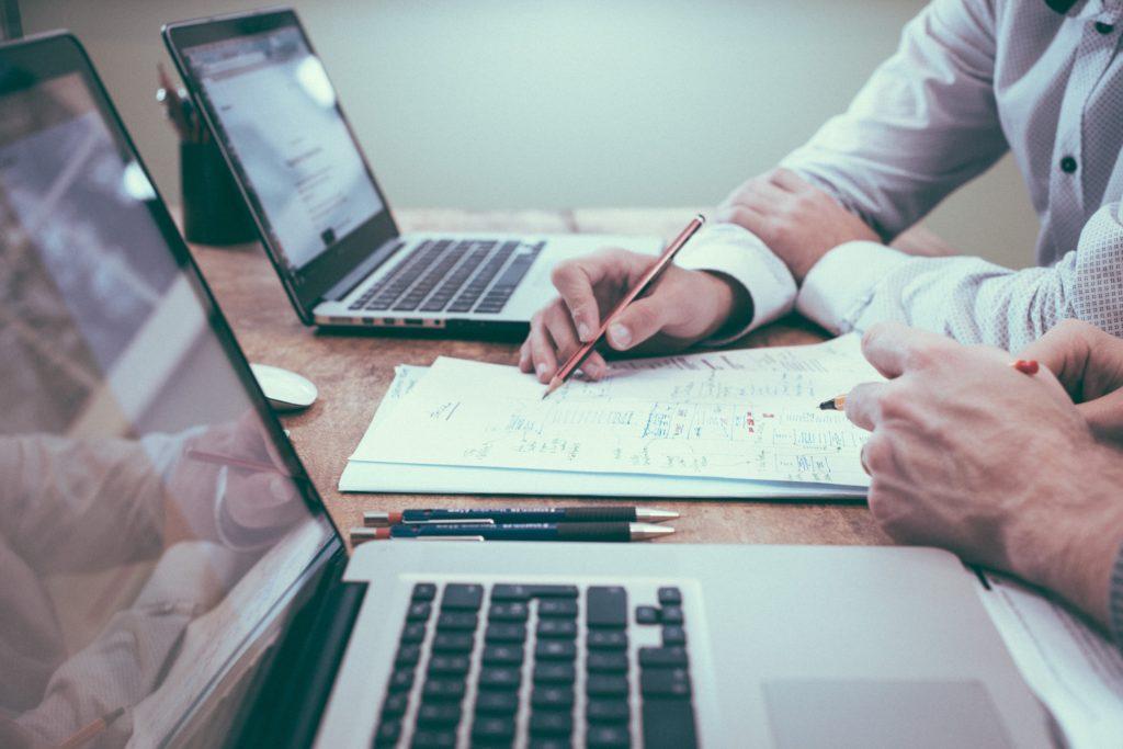 Cette image montre les mains de deux personnes posées sur une table et qui dessinent sur du papier. A côté d'eux se trouvent deux ordinateurs ouverts. On sent qu'ils réfléchissent ensemble sur un sujet en faisant des croquis.